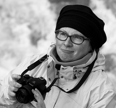 Pictures Of Lily. (Neil. Moralee) Tags: neilmoralee svalbardnorwaylongyearbyenneilmoralee woman mature smile glasses hat coat camera sony lilly thewho townsend mono black white bw blackandwhite nikon d7100 neil moralee cold happy photographer picture portrait girl lady female arctic winter beauty face candid svalbard longyearbyen norway snow glaciers who lily