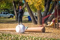Amanda standing on a big baseball.