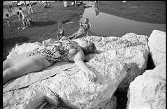 (Sleeping Giant) (Robbie McIntosh) Tags: leicamp leica mp rangefinder streetphotography 35mm film pellicola analog analogue negative leicam analogico blackandwhite bw biancoenero bn monochrome argentique dyi selfdeveloped filmisnotdead autaut candid strangers leicaelmarit28mmf28iii elmarit28mmf28iii elmarit 28mm arsimagofd arsimagofddeveloper arsimagofd159 seaside mappatellabeach rocks lidomappatella ilforddelta100 ilford delta woman sleeping