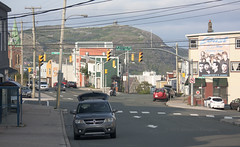 Views from Anywhere (Loops666) Tags: stjohns city urban downtown dodgecaravan minivan mommymobile signalhill cabottower wires telephonepole buildings cars street road crosswalk busstop ad