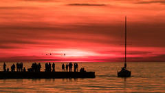 Let's party on jetty (Massimo Buccolieri) Tags: red trieste jetty sunset party silhouette