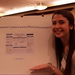 A student posing with her research poster.