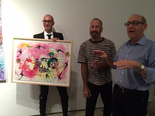 Aric Kurzman presents the 10 year anniversary print for the Adrienne Arsht center by Kenny Scharf, with Kenny Scharf and Fred Snitzer at the Snitzer Gallery