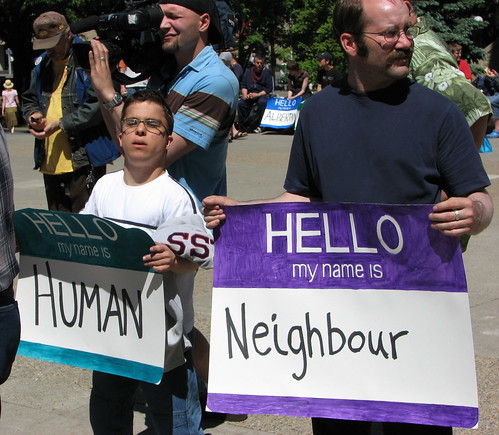 Two people participating in a disability pride event. They are holding up large versions of 'hello, my name is...' stickers like those people wear to events. One's says 'hello my name is: human' and the other's says 'hello my name is: neighbor.'