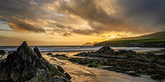 Rocky Beach (Tony Steinberg Photography) Tags: ocean travel ireland sunset sea sky sun sunlight seascape color colour green art beach water beautiful rock clouds skyscape landscape outside outdoors island gold grey golden bay photo sand pretty waves glow quiet shine image horizon fineart creative scenic peaceful scene hills erosion coastal environment coastline serene photographicart setting picturesque tidal tranquil isolated magnificent inspiring shimmer distant countykerry iveraghpeninsula stfinansbay 20x10 â©2013 copyrightarsteinbergallrightsreserved
