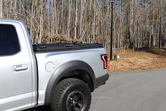 A Heavy Duty Truck Bed Cover On A Ford F150 Raptor (DiamondBack Truck Covers) Tags: aluminum tonneaucover truckbedcover diamondback diamondplate pickuptruck lightgrayorsilvertruck ford f150 raptor ff15 c ruggedblack hd heavydutytruckbedcover 0015000001fxaxyaah noaccessories outdoors woods closed cantedview