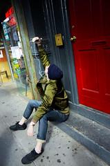 greenjacket (hannah.ghorashi) Tags: nyc newyorkcity boy man guy green hat sitting outdoor sidewalk jeans jacket daytime satin confusion earphones