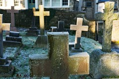 St. John's Churchyard in Frost (john atte kiln) Tags: graveyard gravestones crosses crucifxes leaning shadows sunny frome somerset england unitedkingdom uk britain stone frost lichen cross church mendip religion christianity bokeh unfocused textures stjohnschurch cold