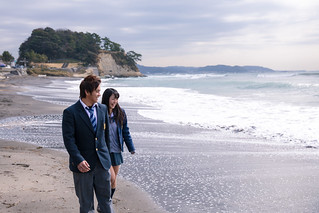 High school student couple walking together at beach