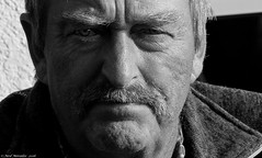 Intense. (Neil. Moralee) Tags: neilmoralee svalbardnorwaylongyearbyenneilmoralee manface close crop moustache intense stare eye eyes mono monochrome black white bw blackandwhite outdoor portrait candid man mature old fisherman neil moralee nikon d7100 18300mm zoom bright shadow face frown intensity people