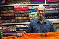 Mizanur Rahman and his colourful fabric (haqiqimeraat) Tags: shopkeeper business dhaka bangladesh street people portraiture portrait