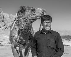 A man and his camel (tmeallen) Tags: portrait blackandwhite man classic look iran profile dromedary camel distant limestonecliffs naqsherostam