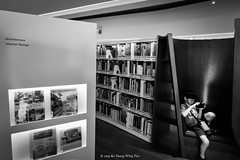 Boy Playing With Mobile Phone In Library (Wing Yau Au Yeong) Tags: boy playing game mobile sitting child phone library streetphotography books games using gaming shelves handphone