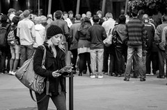 Priorities (midgley.derek) Tags: dsc8635 beautiful woman girl lady single walking street photography different separate crowd spectators priorities interested disinterested smoking addiction tickets reading study concentration melbourne southbank