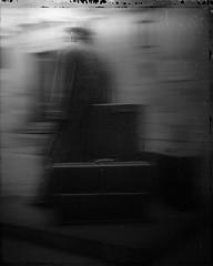 Light In Sight, Jan 2017 (Lumière Passagère) Tags: 4x5 hat suitcase mallet traveler case dark blackwhite smear blur bokeh city plaza coat rain northspain asturias grain bronze metal sculpture
