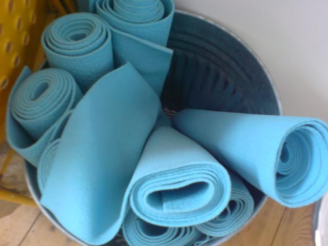 Yoga mats in a bin
