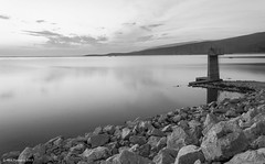 Emotional (Nick Panagou) Tags: longexposure sunset sky lake reflection water clouds contrast landscape lights blackwhite rocks outdoor artificial greece waterscape greatphotographers superphotographer silhouettesshadows bestshotoftheday magnesia canon400d bestphotographer mtpelion shadowssilhouettes spiritofphotography canonefs1855mmf3556isii cloudsstormssunsetssunrises