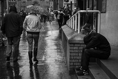 Still Got The Blues (Leanne Boulton) Tags: life street city uk winter light shadow people urban blackandwhite bw white man black detail reflection male texture wet monochrome rain weather canon mono scotland living blackwhite hoodie mood sitting natural emotion humanity outdoor glasgow candid culture streetphotography scene human shade 7d isolation feeling 40mm misery hiding raining society desolate tone sociallandscape candidstreetphotography ef40mmf28stm