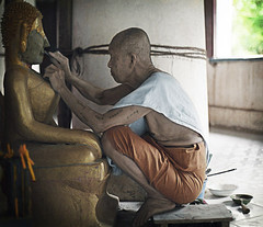 A monk paints the Buddha statue at a monastery in Laos