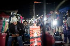 A local checking his phone at Luang Prabang night market, Laos (Sitoo) Tags: laos luangprabang asia southeastasia people gente portrait mercado nocturno nightmarket night market local nightphotography nightshot nightlife nightlights shops seller phone teléfono hat sombrero