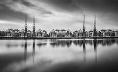 Reflecting at Victoria Docks (Nathan J Hammonds) Tags: victoria dock london east docks cranes monochrome reflection nikon d750 long exposure nd 10stop buildings architecture water calm clouds