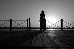 (cherco) Tags: woman mujer blackandwhite blancoynegro backlighting sea mar silhouette shadow silueta sombra lonely solitario wood bridge hair wind viento pelo sunset sunny composition composicion canon sky