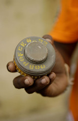 A P-4 Pakistani anti-personnel mine is held by a deminer