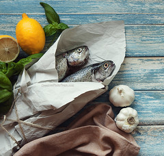 fish (CreativePhotoTeam.com) Tags: wood old blue food fish green cooking nature kitchen closeup dinner silver river paper cuisine wooden lemon healthy rainbow fishing raw natural market background fat omega rustic towel fresh retro delicious eat health spices meal garlic packaging basil seafood trout diet fin calorie freshness aroma nutrition