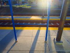 Light Rail platform (Zombie37) Tags: blue sun color lines yellow contrast glare bright vivid rail baltimore minimal poles concrtete