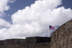 Flag waves over historic military fort. (Guy dicarlo) Tags: fort flag american historical puerto historic military rico war monument history national north landscape old travel architecture rican america wall el morro usa sky clouds pride waving army fortress castle ancient landmark building blue defend strong hold
