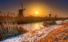 Glowing mill sunrise . (rudi.verschoren) Tags: paars sunrise water exposure winter white sky sun outdoor landscape landschap lines light blue yellow orange colors cold mills mood museum molens morning holland heritage ice snow frozen frost eos europe europa pittoresque image unesco kinderdijk cloudsstormssunsetssunrises