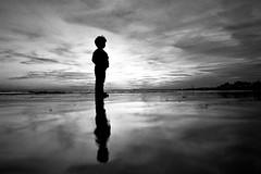 stand tall (fotobes) Tags: boy sea chimney sky blackandwhite reflection beach monochrome silhouette clouds reflections blackwhite lca lomography brighton felix dusk grain lowtide seafront brightonbeach wetsand ratseyeview wetreflections shorehamharbour lomographyladygreybw400 lomographyladygrey