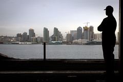 A Sailor looks at the San Diego skyline during a sea and anchor evolution. (Official U.S. Navy Imagery) Tags: usstheodoreroosevelt cvn71 vn584 alex corona silhouette sandiego seaandanchor underway sandiegobay