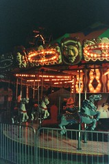 Kitschy Carousel (Anne Abscission) Tags: carnival horses night analog 35mm lights washington availablelight clown lion carousel rides kitschy olympustrip35 amusements everett 400asa carouselhorse sausagefest olympustrip filmphotography ferraniasolaris sausagefestival