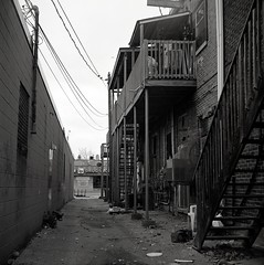 Alley - Windsor (paulgumbinger) Tags: yashica yashicad tlr fuji acros 100 120mm film medium format blackandwhite monochrome windsor alley fire escape ontario drug store garbage