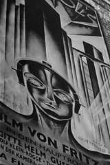 Maschinenmensch (UberJ) Tags: blackandwhite bw building slr film wall 35mm canon movie poster outdoors ae1 maria grain delta d76 400 metropolis ilford fritzlang delta400 canonfd70210f4