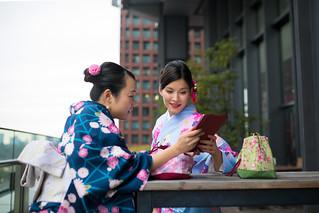 Multi ethnic group of women in kimono watching screen on digital tablet