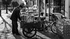 Bike 33/52 (Go-tea 郭天) Tags: street urban city outside outdoor people bw bnw black white blackwhite blackandwhite monochrome asia asian china chinese canon eos 100d 24mm prime qindao huangdao 52 52project 33 bike bicycle 3 weels wheels saler shop cold morning preparation preaparing ready cook cooking sweet potatoes man old alone coat warm hot fire farmer back mobile fixed sun light shadow trees food