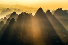 Lightburst (One_Penny) Tags: china morning travel houses light sky sun mountains color colour nature yellow sunrise canon landscape photography asia village yangshuo horizon shades hills layers tones karst lightrays guangxi 6d xingping damianhill