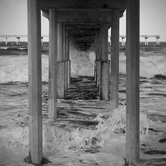 under the pier B&W (BorrowedLightPhoto) Tags: blackandwhite water pier waves under foam crop splashing oceanbeachpier