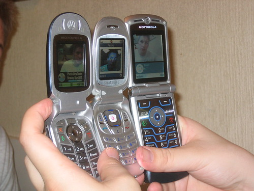 A user holding three different cell phones