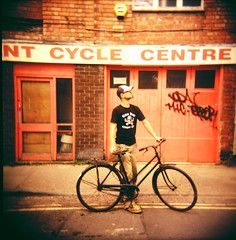 A True Clunker (George Pollard) Tags: street portrait 120 bike bicycle june vintage mediumformat square bill holga discount xpro crossprocessed northampton squares nt centre 2006 cycle kaiser clunker totenkopf chopperclub cfn deathgob derbyroad snappysnaps sugarskullcycles wwwsugarskullcyclescom adventure09
