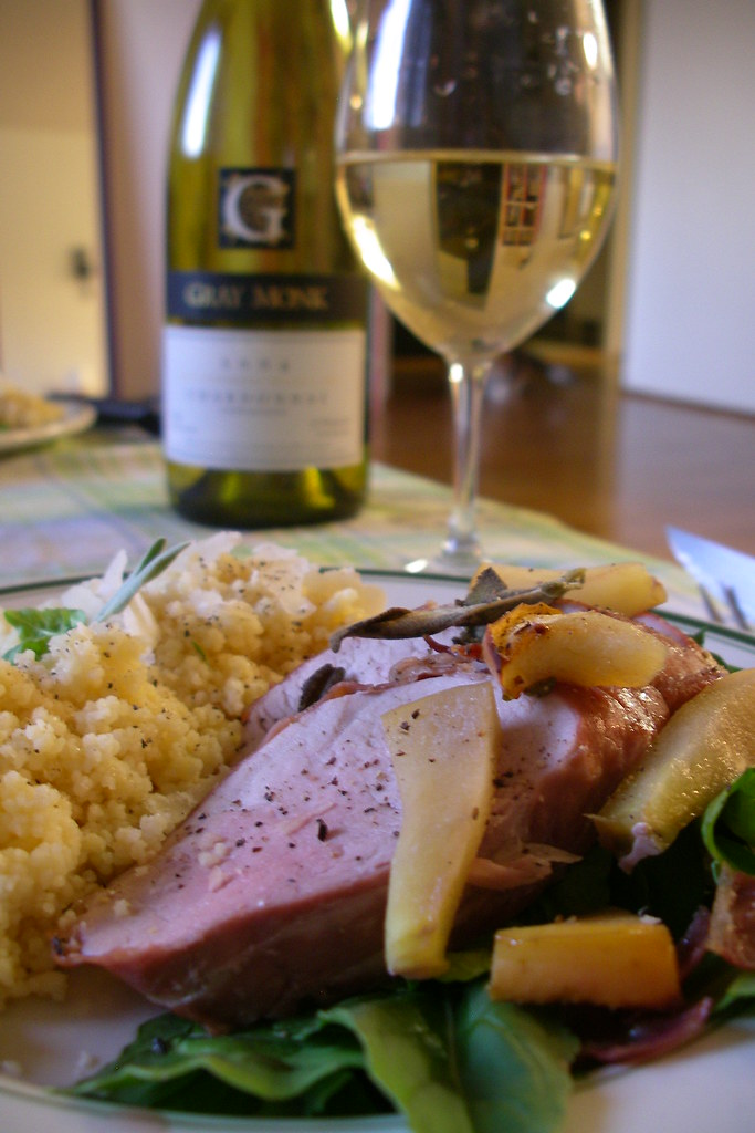 proscuitto-wrapped pork loin on apples and arugula with parmesan couscous