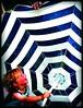 the hand that rocks the ... (kiplingflu) Tags: blue summer white colors topv111 kids laughing umbrella hand belgium fav1025 favme 2006 fv10 laughter belgica couleur kleur quinten e500 i500 froy