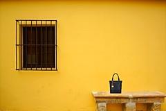 Forgotten ? (jo.misere) Tags: windows black yellow bench bag spain bars bank ronda tas geel zwart minimalistic raam spanje tralies minimalistisch