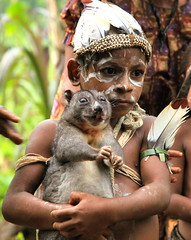 Boy at Wasana Hunting Camp Holds a Cuscus in his Arms