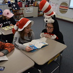 Student helps elementary student read a book