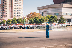 Policeman Blocking the road access to parade area (reubenteo) Tags: city red tourism war asia fireworks military korea parade communism celebration kimjongil vip metropolis comrade socialism tanks workersparty northkorea pyongyang 70thanniversary dprk kimilsung kimjongun