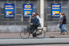 Hold on tight - Amsterdam (tim jg photography) Tags: road family man holland love netherlands amsterdam speed standing fun movement holding europe dad cyclist child lift close pavement wheels transport daughter blurred pedestrians bond pedals passenger shoulders protect holdingon