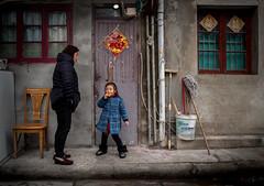 granny looking for the door key (Rob-Shanghai) Tags: lane shanghai doorkey people girl kids granny china street leicaq